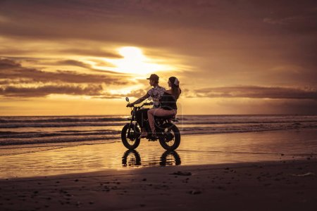 couple riding motorcycle into ocean during sunrise