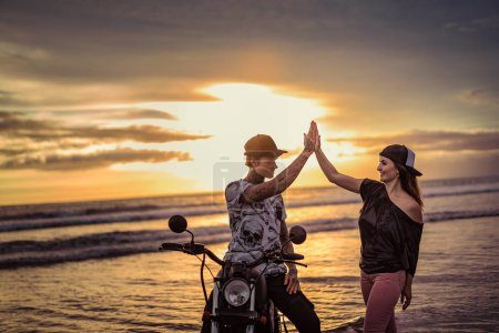 boyfriend and girlfriend giving high five near motorcycle on ocean beach