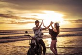 couple giving high five near motorcycle on ocean beach during sunrise