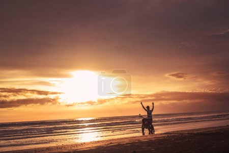 Photo for Biker standing near motorbike with hands up and looking at beautiful sunrise - Royalty Free Image