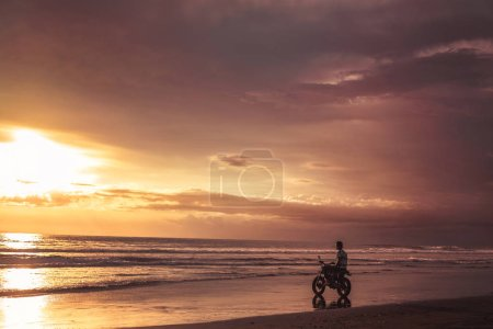 man sitting on motorbike on seashore and looking at beautiful sunset
