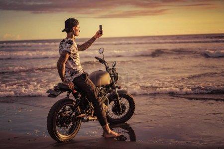 Photo for Tattooed man sitting on motorbike at seashore and taking photo of sunrise with smartphone - Royalty Free Image