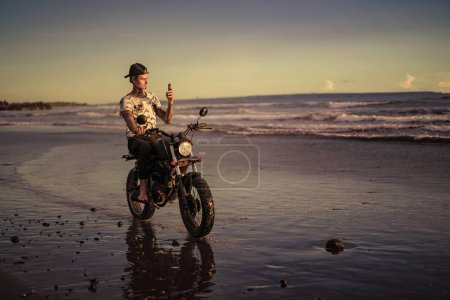 Photo for Tattooed biker sitting on motorbike on ocean beach and taking photo of sunrise with smartphone - Royalty Free Image