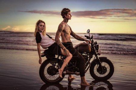 couple posing on motorcycle on ocean beach