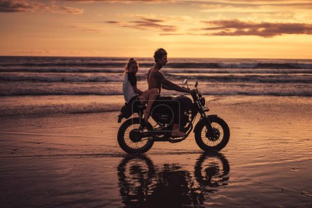 Photo pour Couple de moto sur la plage de l'océan - image libre de droit