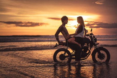 girlfriend touching shirtless boyfriend on motorbike at beach during sunset