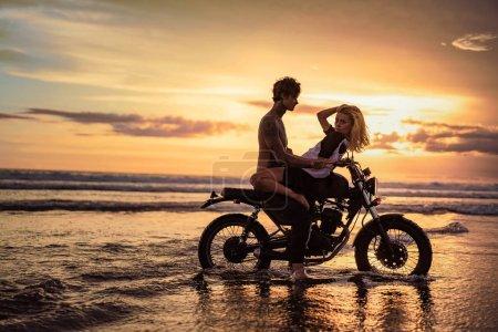 Photo pour Vue latérale du couple passionné câlins sur la moto sur la plage pendant le coucher du soleil - image libre de droit