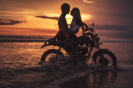 Photo for Passionate couple hugging on motorbike at beach during sunset - Royalty Free Image