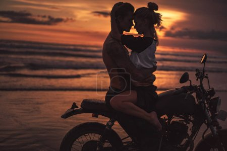 Photo for Shirtless boyfriend hugging girlfriend on motorcycle at beach during sunset - Royalty Free Image