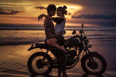 Photo pour Couple passionné câlins sur la moto sur la plage pendant le coucher du soleil - image libre de droit