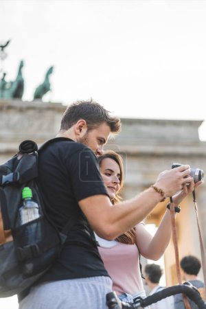 tourists looking at photo camera in front of Brandenburg Gate, Berlin, Germany