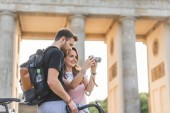 low angle view of woman showing photo camera to boyfriend at Pariser Platz, Berlin, Germany