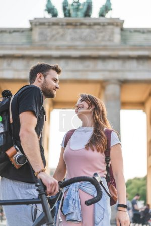 low angle view of travelers with backpacks and bicycle in front of Brandenburg Gate, Berlin, Germany