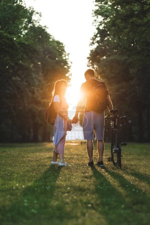 Photo for Couple with backpacks and bicycle standing on meadow with setting sun behind - Royalty Free Image