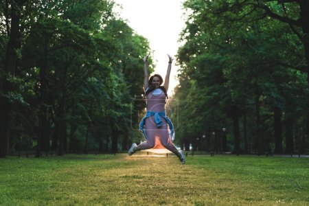 Photo pour Jeune femme sautant avec de larges bras sur la prairie dans le parc - image libre de droit
