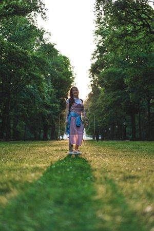 Photo pour Vue faible angle de souriante jeune femme regardant la caméra sur Prairie avec arbres - image libre de droit