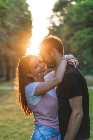 Photo for Smiling young woman embracing boyfriend and looking at camera with sunset behind - Royalty Free Image