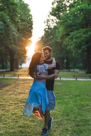 smiling man holding young girlfriend in park during sunset time