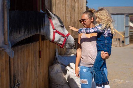 mother and daughter palming horse at farm