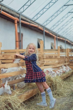 smiling kid standing at farm with goats