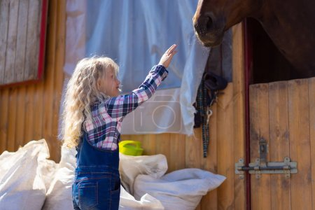 side view of kid going to touch horse at farm