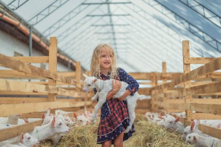 smiling adorable kid holding goat at farm