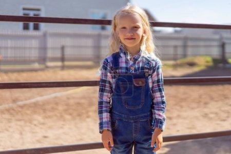 Photo pour Adorable gamin debout près de la clôture à la ferme et en regardant la caméra - image libre de droit