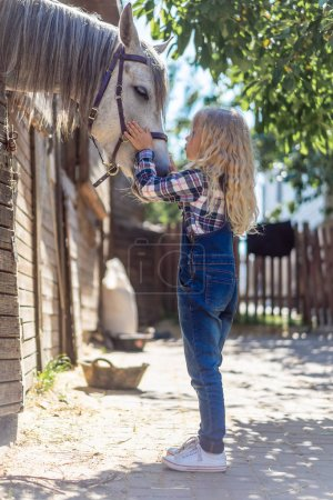 side view of kid going to kiss white horse at farm
