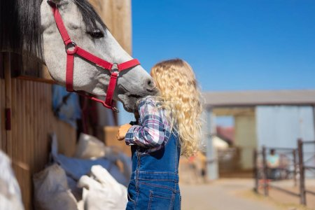 kid hugging horse near stable at farm