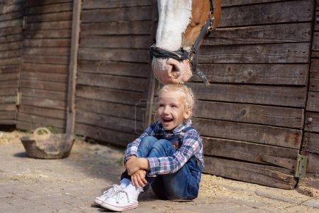 Photo pour Enfant heureux assis sur le sol et cheval toucher ses cheveux à la ferme - image libre de droit
