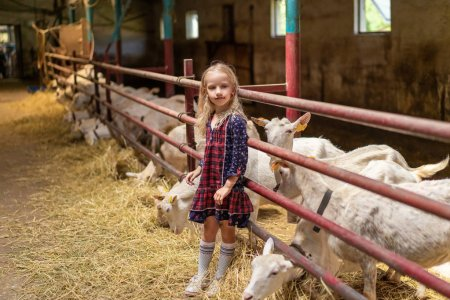 adorable kid leaning on fences in barn and looking away