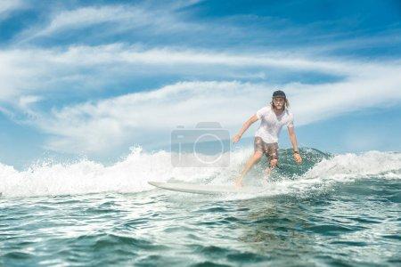 Foto de Guapo deportista masculino de surf sobre las olas en el océano en la playa de Nusa Dua, Bali, Indonesia - Imagen libre de derechos