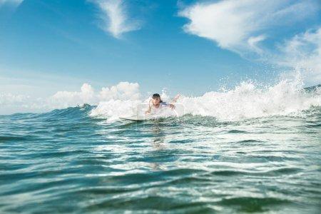 Foto de Masculino surfista nadando en el tablero que practica surf en el océano en la playa de Nusa Dua, Bali, Indonesia - Imagen libre de derechos