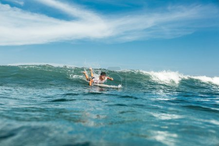 Foto de Vista del deportista masculino de la natación en el tablero que practica surf en el océano en la playa de Nusa Dua, Bali, Indonesia - Imagen libre de derechos