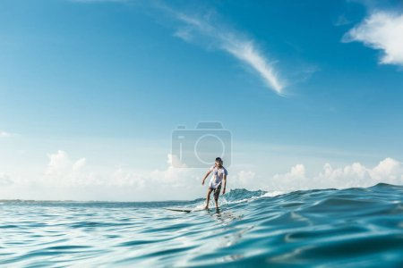 distant view of male surfer riding on surfing board in ocean at Nusa Dua Beach, Bali, Indonesia