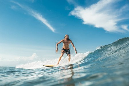 shirtless male surfer riding waves in ocean at Nusa Dua Beach, Bali, Indonesia