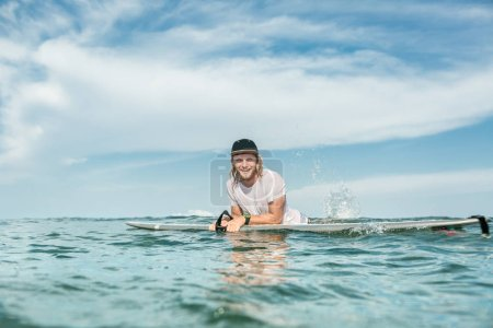 smiling male surfer resting in ocean with surfing board at Nusa Dua Beach, Bali, Indonesia