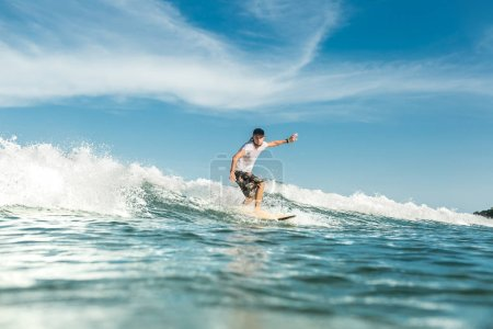 young male surfer riding waves in ocean at Nusa Dua Beach, Bali, Indonesia