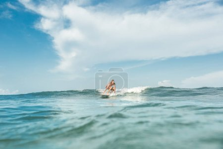 distant view of shirtless male surfer riding on board in ocean at Nusa Dua Beach, Bali, Indonesia