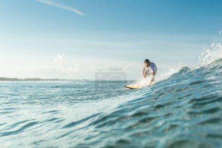 Foto de Enfoque selectivo de surfer hombre montar a bordo en el océano en la playa de Nusa Dua, Bali, Indonesia - Imagen libre de derechos