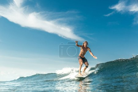 handsome shirtless male surfer riding waves in ocean at Nusa Dua Beach, Bali, Indonesia