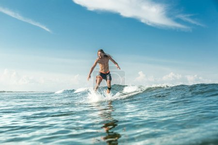 Photo for Shirtless male surfer riding on surfing board in ocean at Nusa Dua Beach, Bali, Indonesia - Royalty Free Image