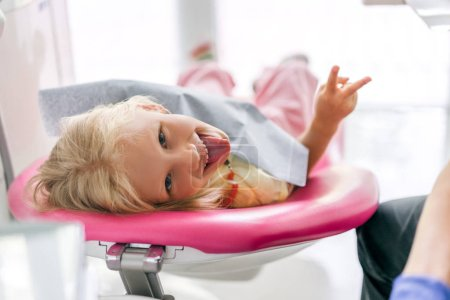 Photo pour Portrait d'enfant, coller la langue dehors et signe de paix montrant au bureau de dentiste - image libre de droit