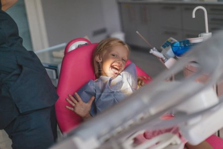 partial view of dentist and kid sticking tongue out in chair at dentist office