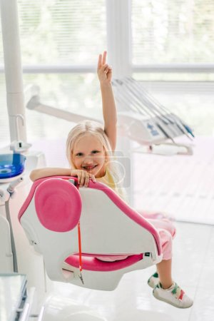 smiling kid showing peace sign while sitting in chair at dentist office