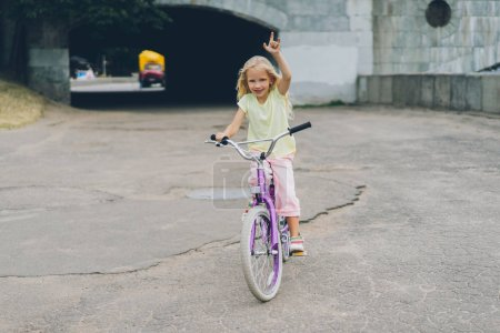 smiling kid with bicycle showing rock sign on street