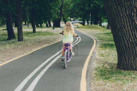 Photo for Back view of blond child riding bicycle on road in park - Royalty Free Image