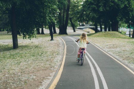 Photo pour Vue arrière de blond enfant à vélo sur la route dans le parc - image libre de droit