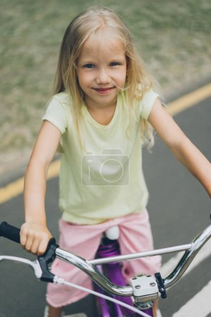 Photo for Portrait of smiling kid on bicycle looking at camera on street - Royalty Free Image