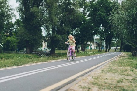 little child riding bicycle on road in park on summer day